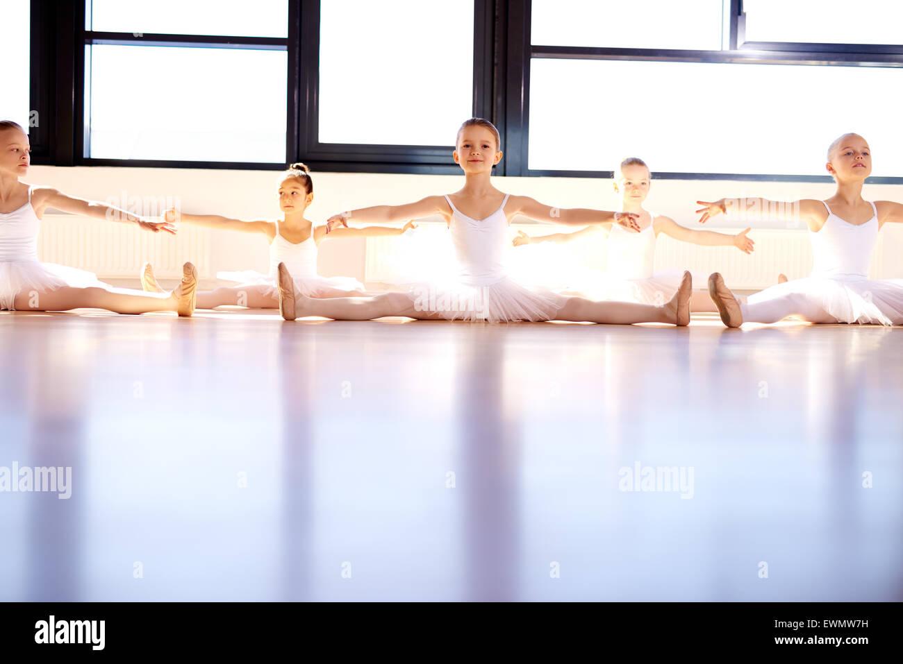Grupo de niñas en un estudio de ballet vestidas de blanco tutus sentados en el suelo practicando con sus brazos Imagen De Stock