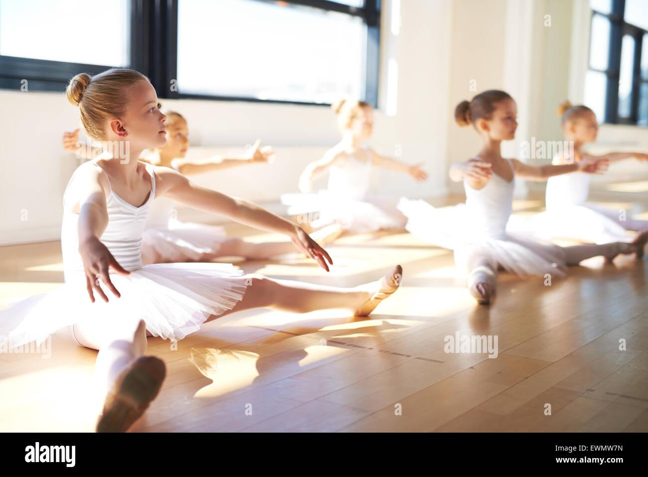 Muchachas jóvenes, vestidos de blanco tutus, sentados en el suelo en el estudio, mientras que con un entrenamiento Imagen De Stock