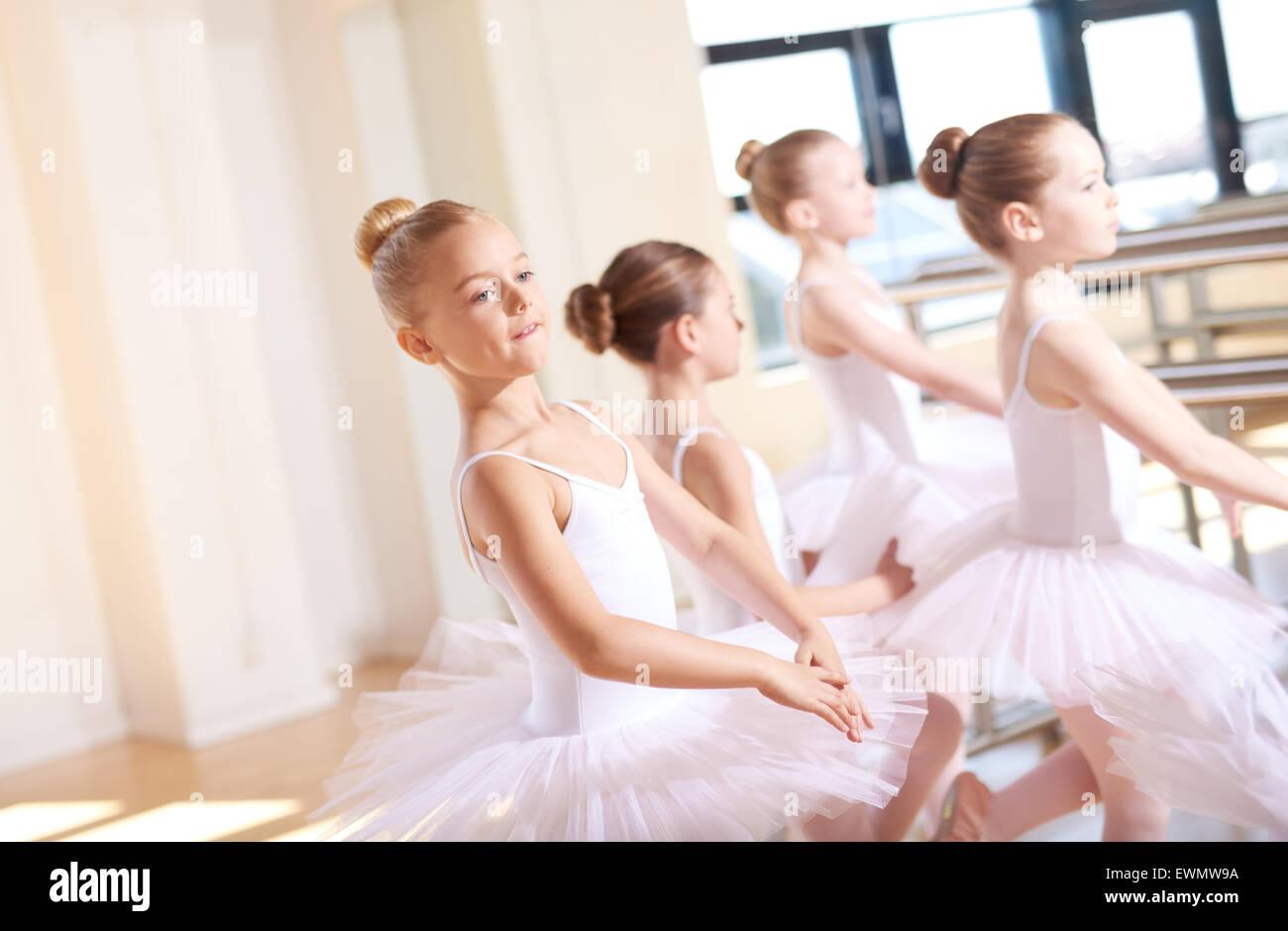 Cute little bailarinas vestidas de blanco tutus, practicando su baile dentro del estudio durante su clase de ballet. Imagen De Stock