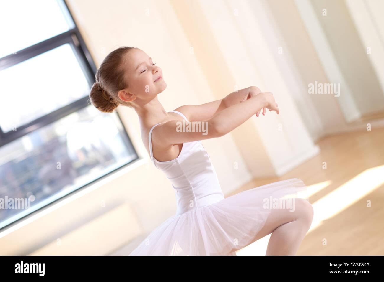 Sonriente niña bonita ballet en blanco tutu practicando un número de baile dentro del estudio por sí Imagen De Stock