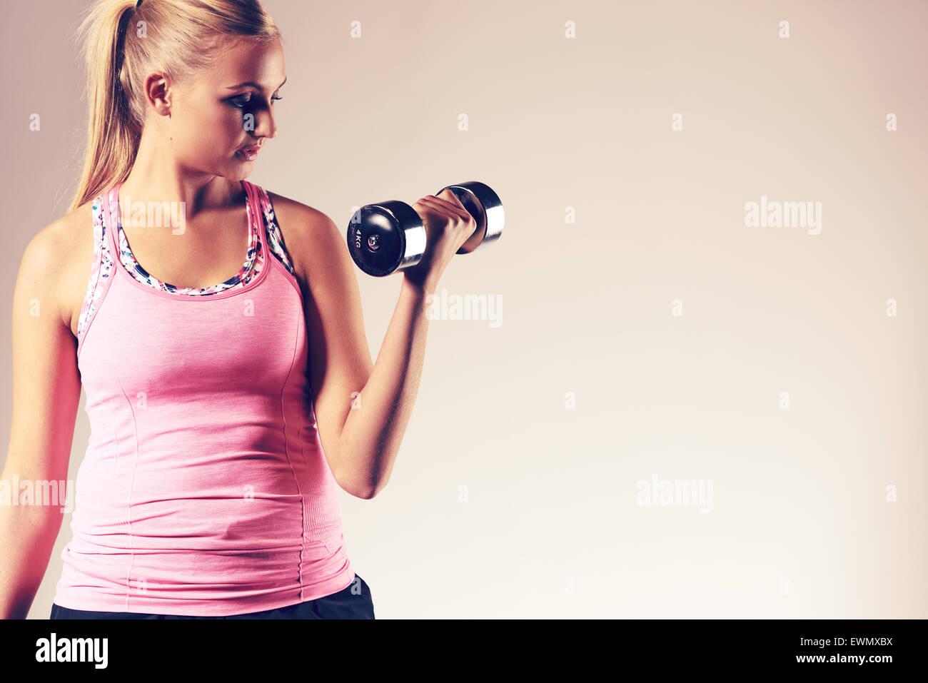 Mujer joven ejercitar la parte superior del cuerpo haciendo un curl bíceps con pesas libres. Imagen De Stock
