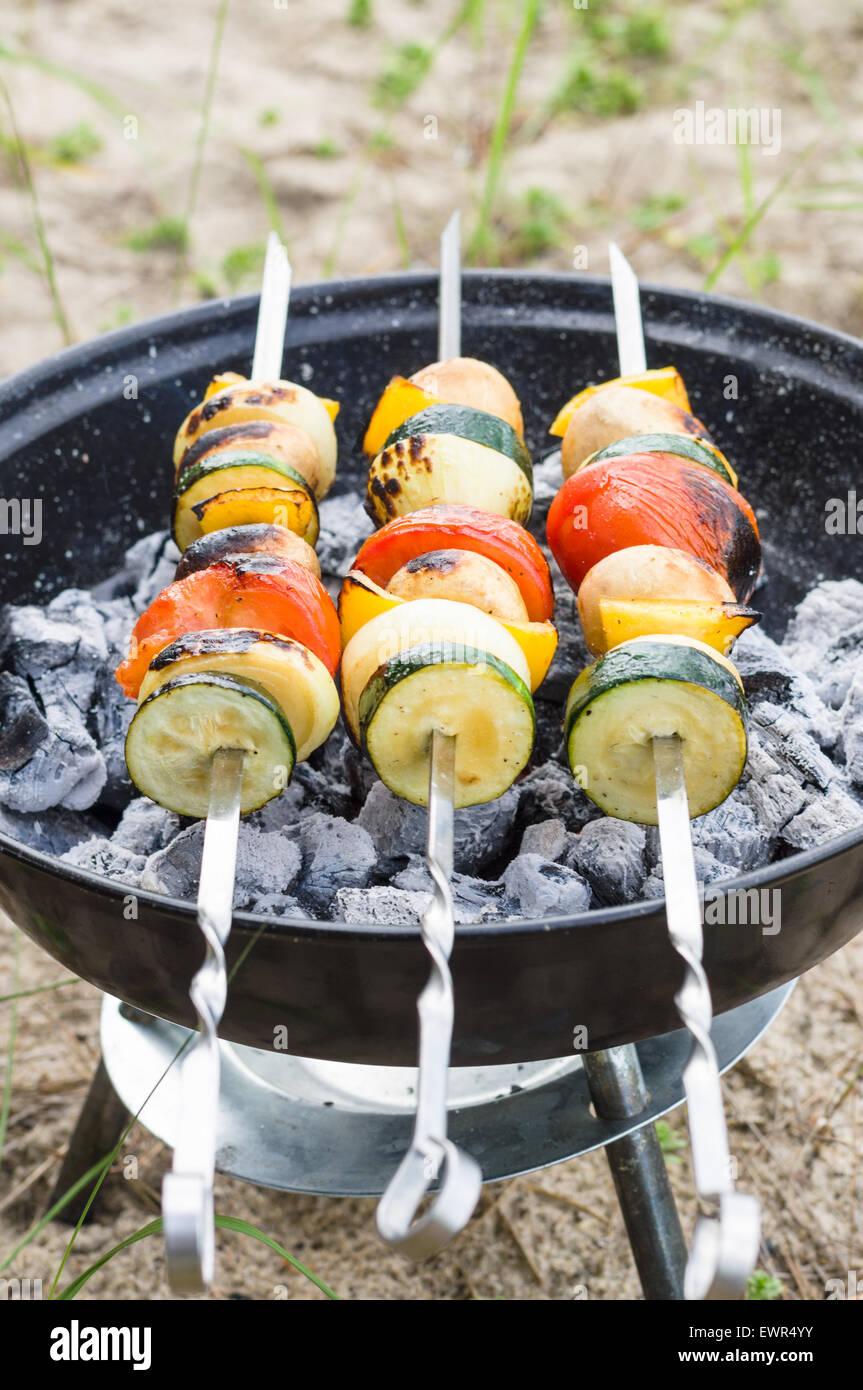 Vegan shish kebab en pincho. Verduras frescas preparadas en una parrilla de carbón vegetal, al aire libre. Imagen De Stock