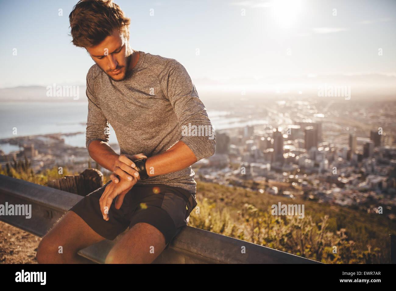Joven de reajustar su reloj GPS antes de una carrera. Colocar joven atleta sentado en la carretera baranda y comprobando Imagen De Stock
