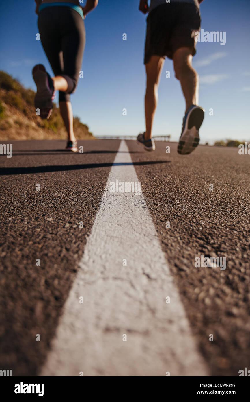 Captura recortada de dos personas corriendo en carretera. Formación de atletas en Country Road. Tiros de ángulo Imagen De Stock