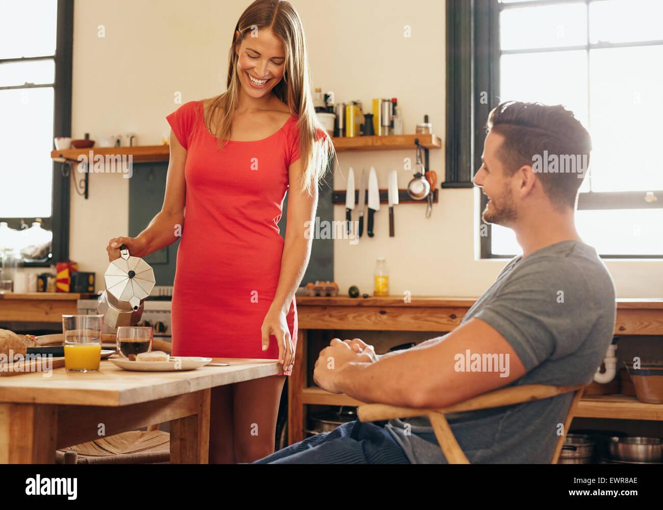 Filmación en interiores de la pareja tomando el desayuno en la cocina. Mujer joven vierte café en una Imagen De Stock
