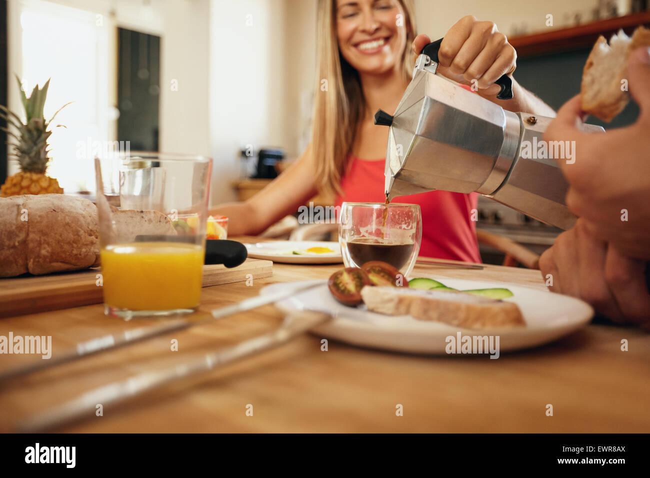 Disparo de interior de mujer vertiendo el café en una taza. Mujer sonriente mientras servía el desayuno Imagen De Stock
