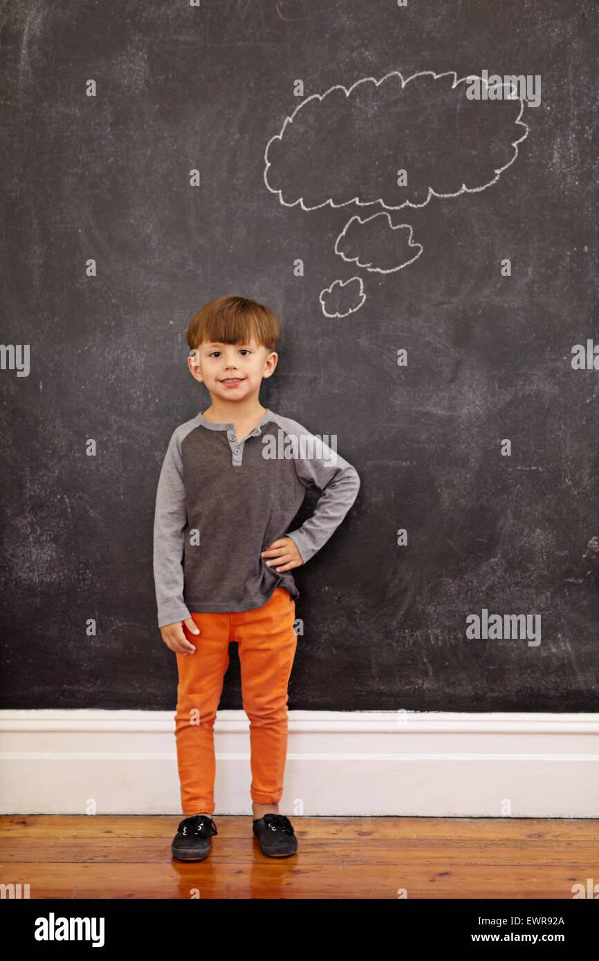 Cute Little Boy con un pensamiento sobre la burbuja de la pizarra. Disparo de longitud completa del joven de pie Imagen De Stock
