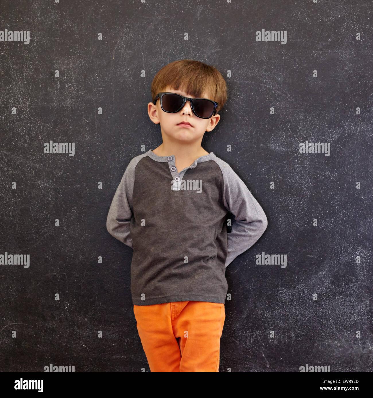 Lindo chico de pie delante de la pizarra. Elegante chico con gafas de sol recostado en una pizarra, buscando en Imagen De Stock