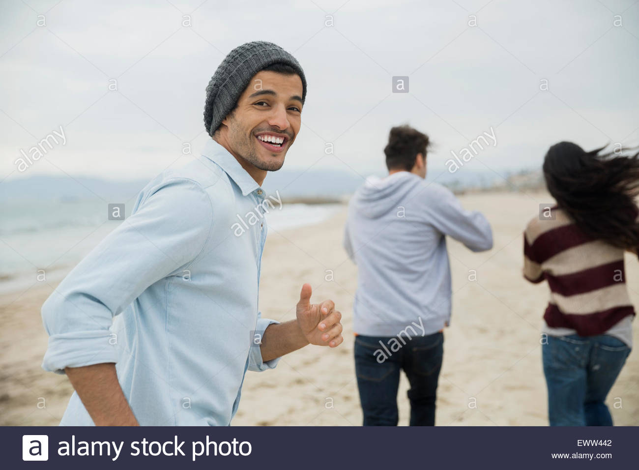 Retrato sonriente hombre corriendo con amigos en la playa Imagen De Stock