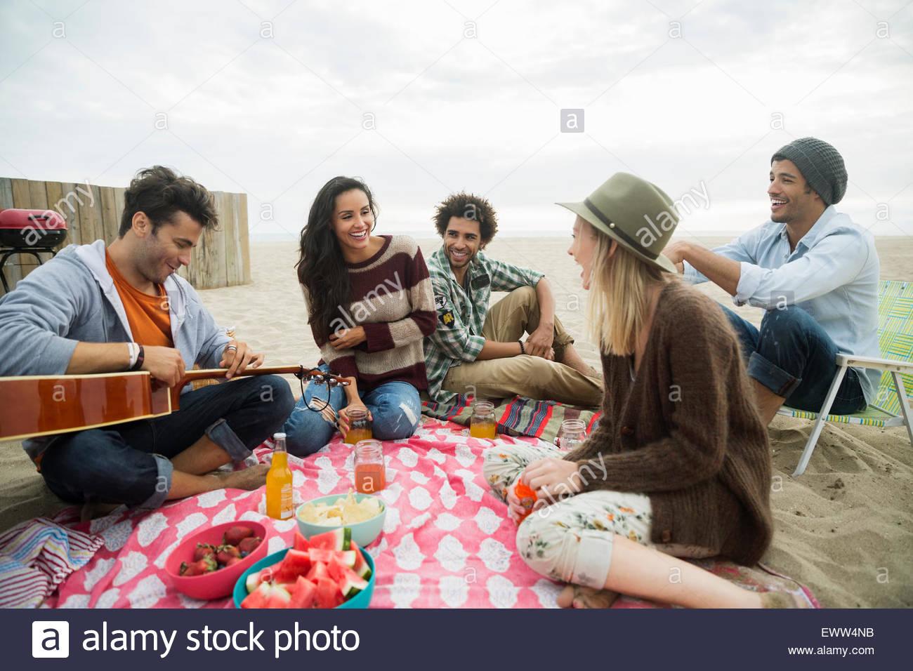 Sus amigos tocando la guitarra picnic en la playa Imagen De Stock
