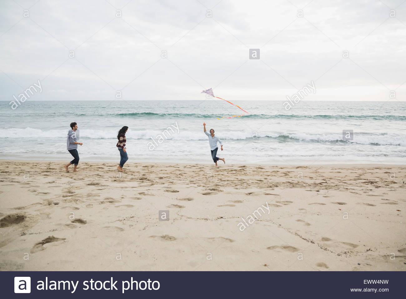 Amigos volar una cometa en la playa Imagen De Stock