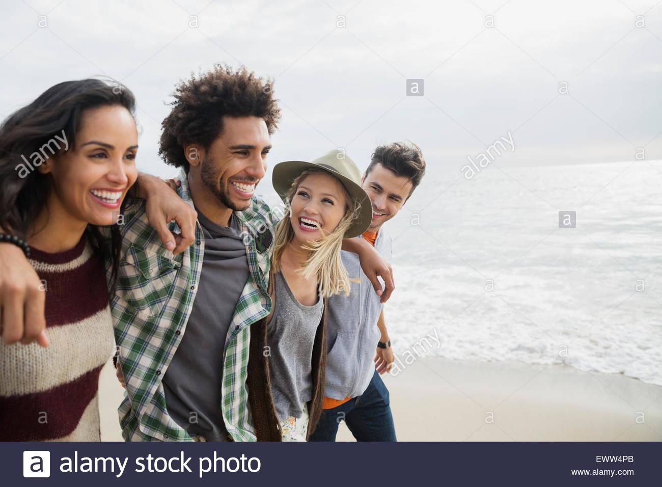 Amigos sonriente caminando en una fila en la playa Imagen De Stock