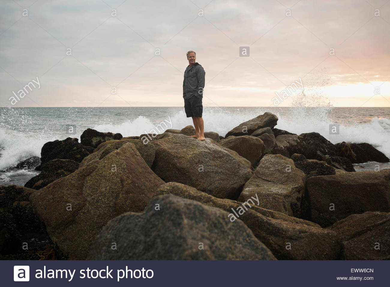 Ocean salpicaduras de rocas detrás de hombre al atardecer Imagen De Stock
