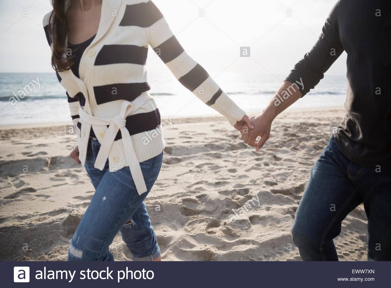 Pareja tomados de la mano y caminar en la playa Imagen De Stock