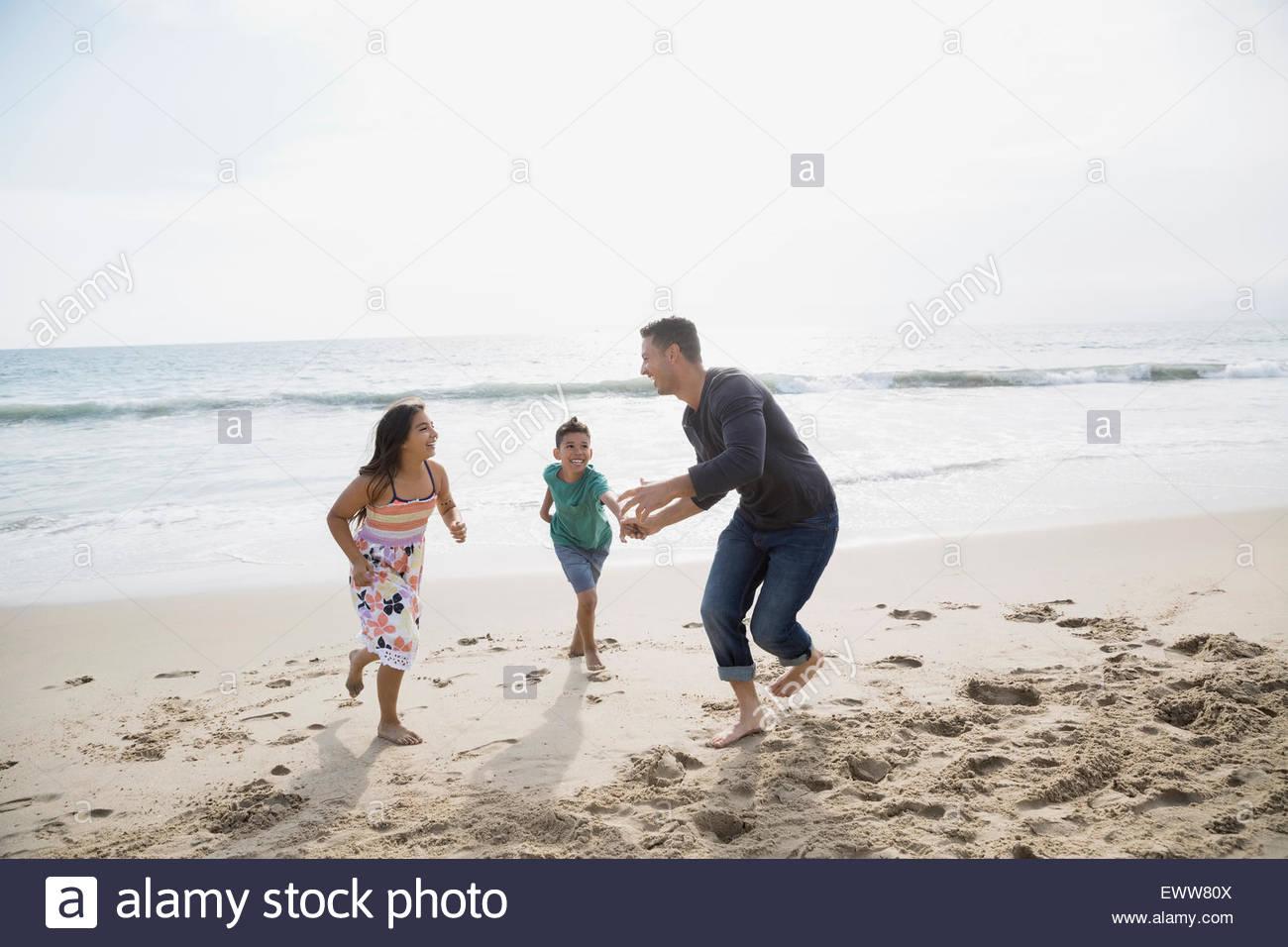 Familia lúdica ejecutando en sunny beach Imagen De Stock