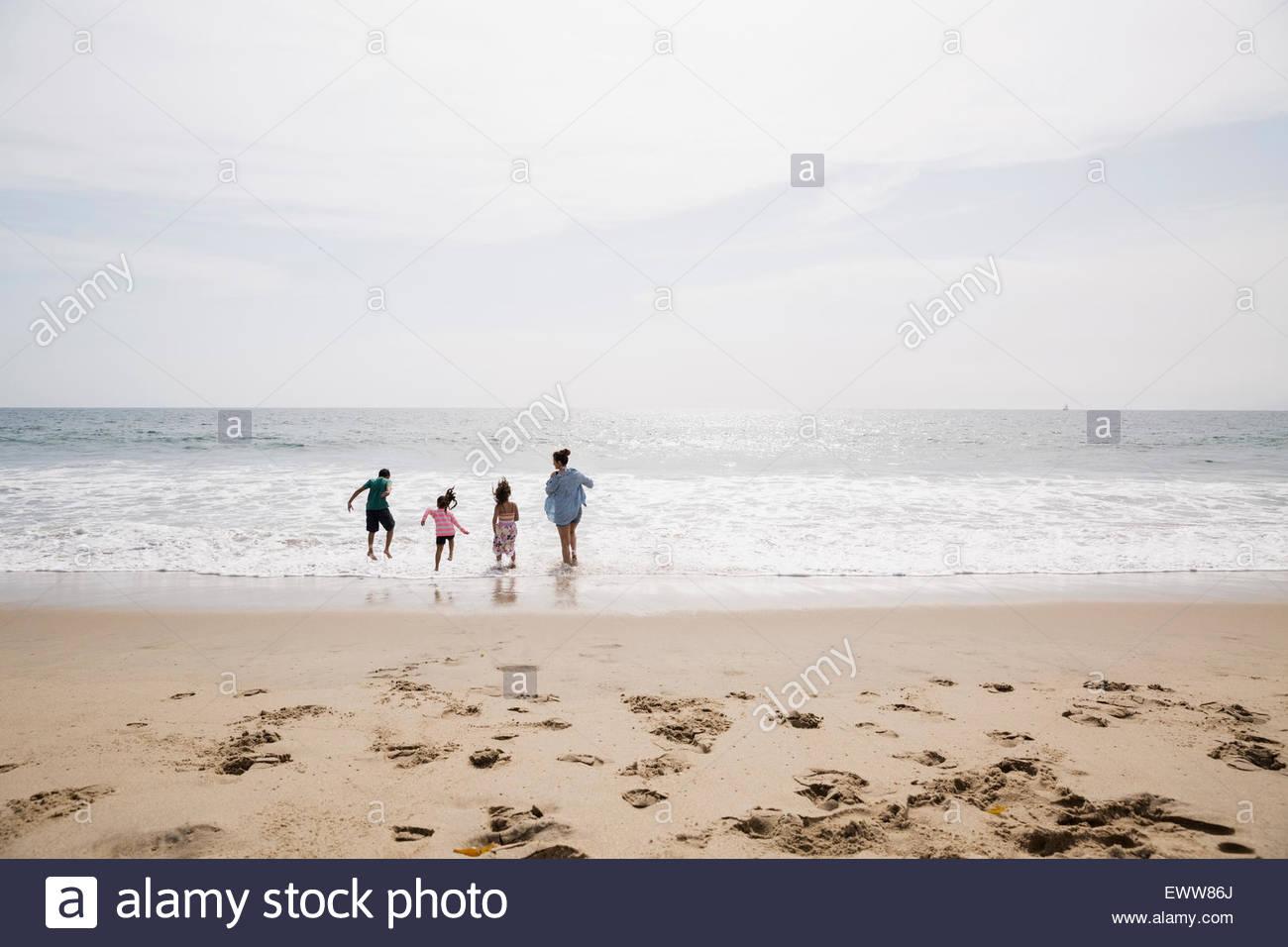 Familia jugando y vadeando en ocean sunny beach Imagen De Stock