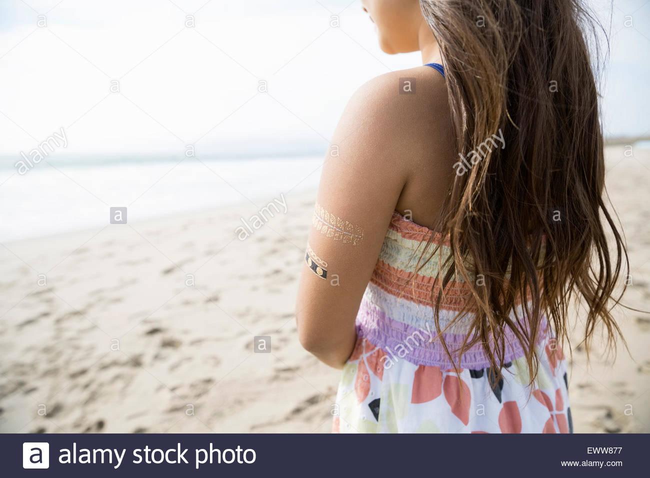 Pensativo chica con tatuajes de henna en el brazo beach Imagen De Stock