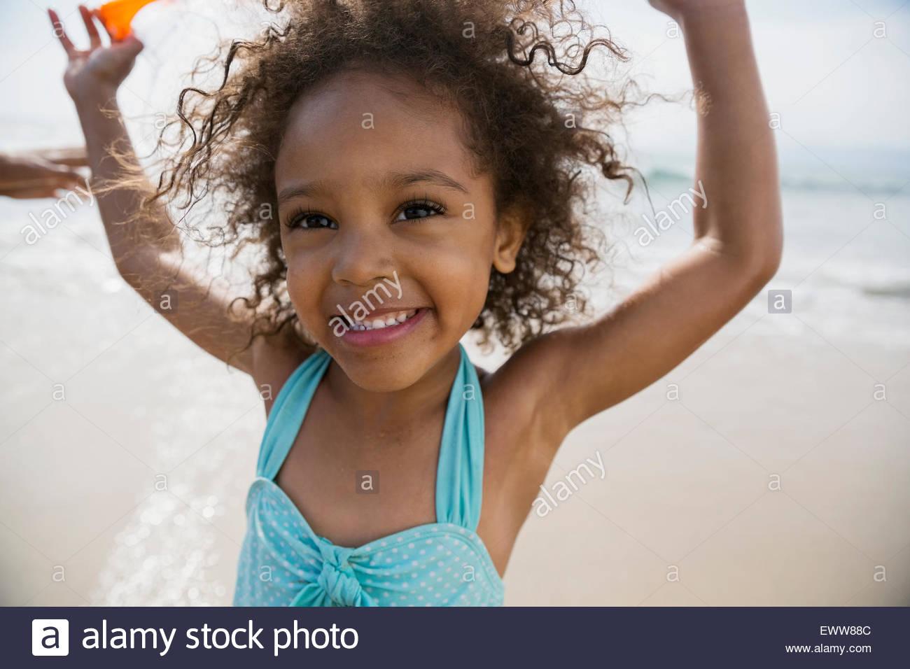 Retrato chica con los brazos levantados en la playa Imagen De Stock