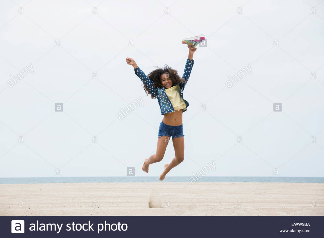 Retrato exuberante chica saltando en la playa Imagen De Stock
