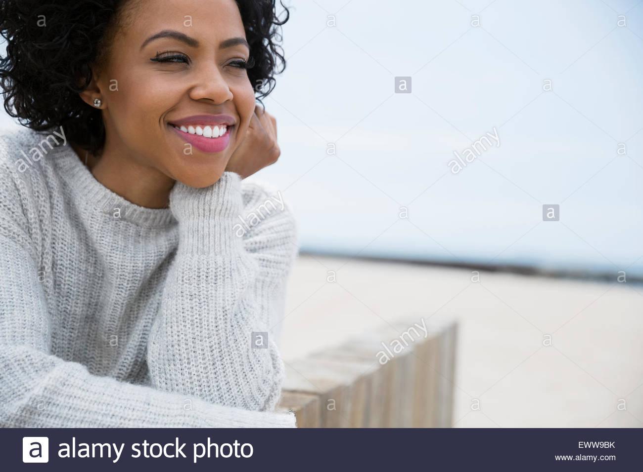 Retrato mujer sonriente rizado cabello negro en la playa Imagen De Stock