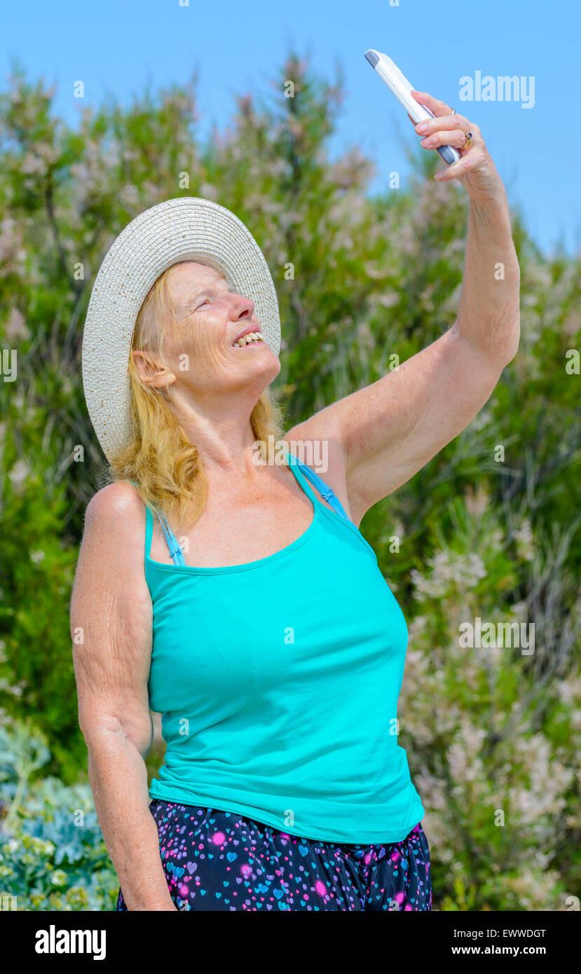 Mujer de mediana edad tomando una foto selfie de sí misma en un día soleado de verano caliente en el Reino Imagen De Stock