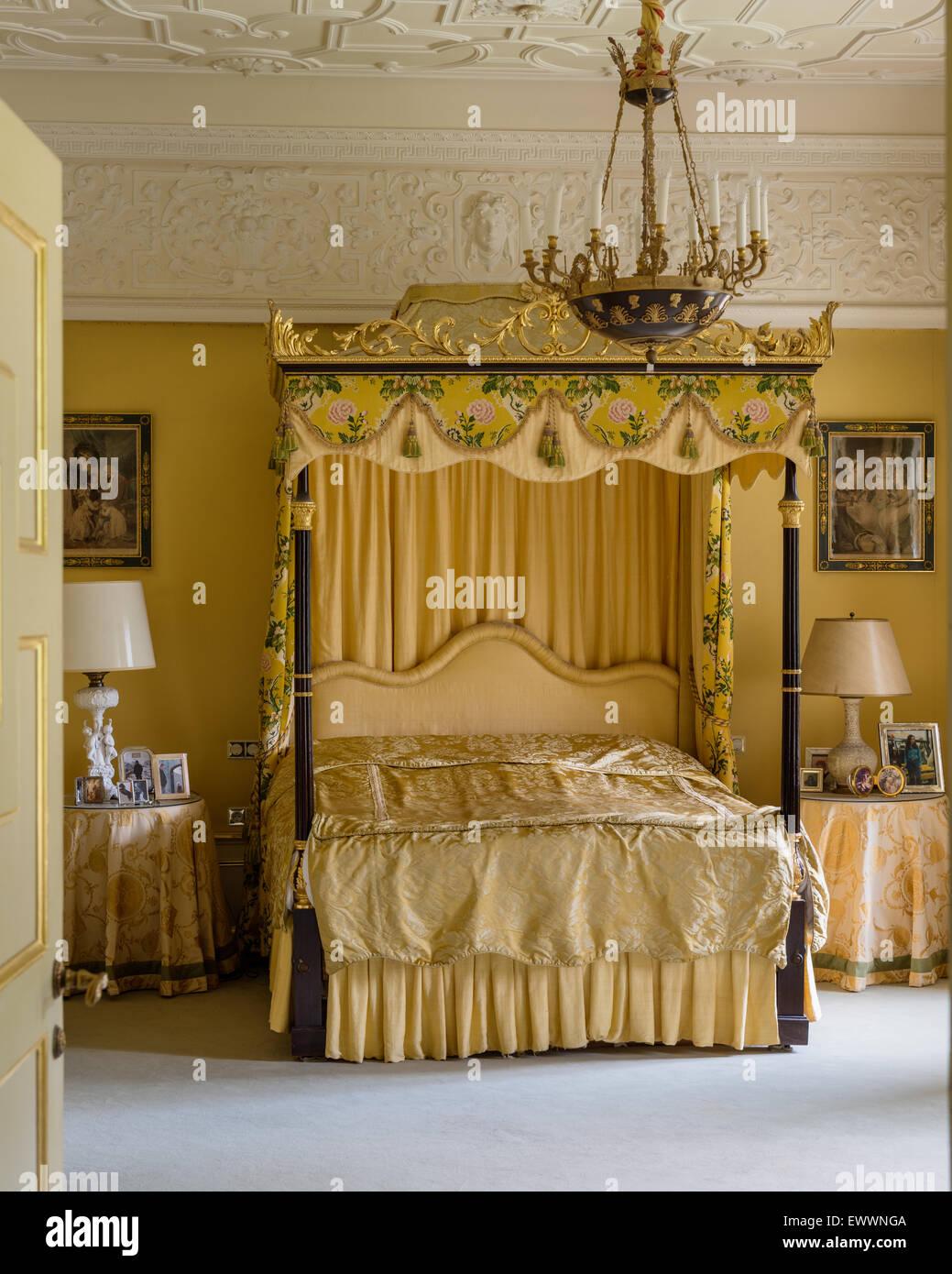 Cama con dosel con marco dorado en el suntuoso dormitorio con techos ...
