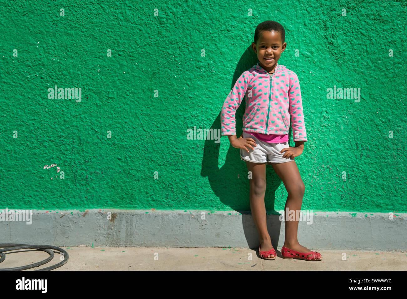 Namibia - joven muchacha africana de pie en frente de la pared verde brillante. Imagen De Stock