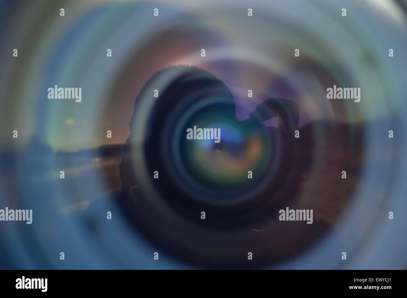 Objetivo y lente con el paisaje y la mano del fotógrafo óptico múltiples reflexiones. Foto de stock