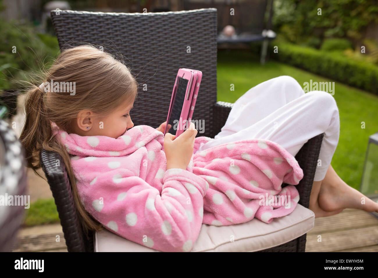 Chica viendo la película sobre dispositivos electrónicos Imagen De Stock