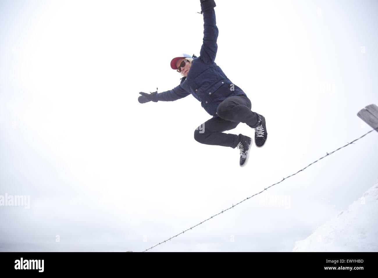 Ángulo de visión baja de un joven saltando sobre valla Imagen De Stock
