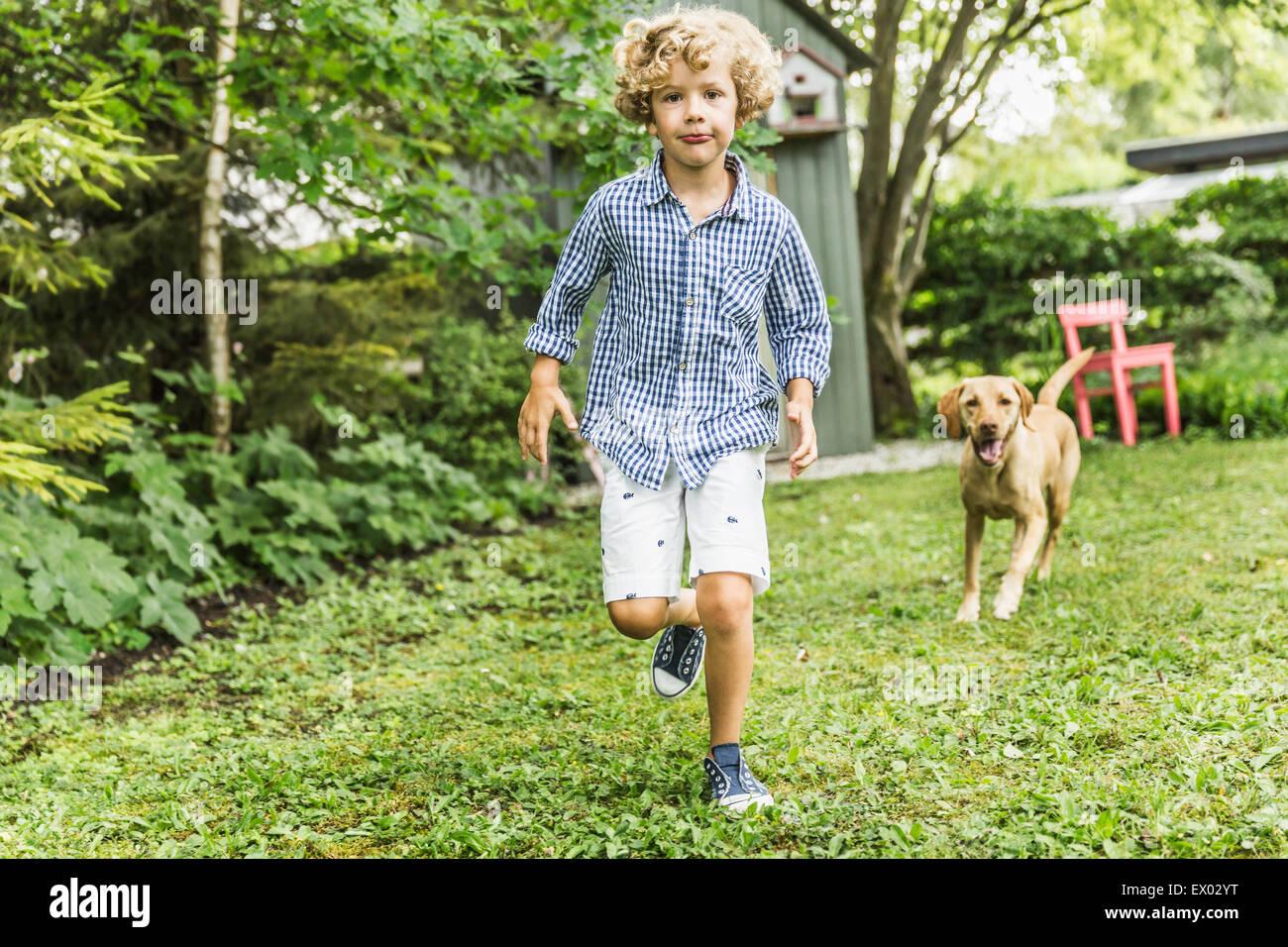 Niño corriendo con el perro en el jardín Imagen De Stock