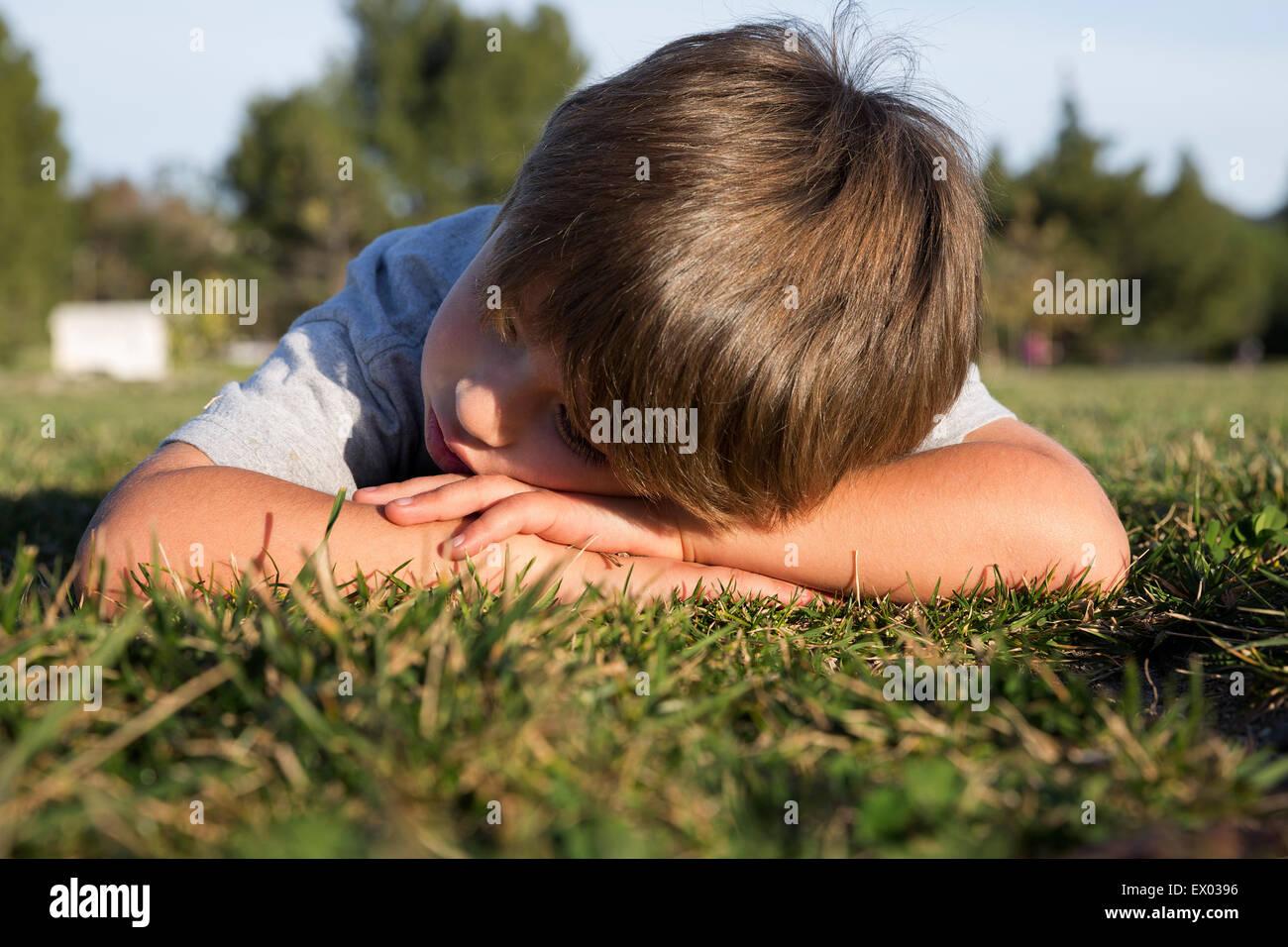Hosco boy con bajar la cabeza recostada sobre la hierba del parque Foto de stock
