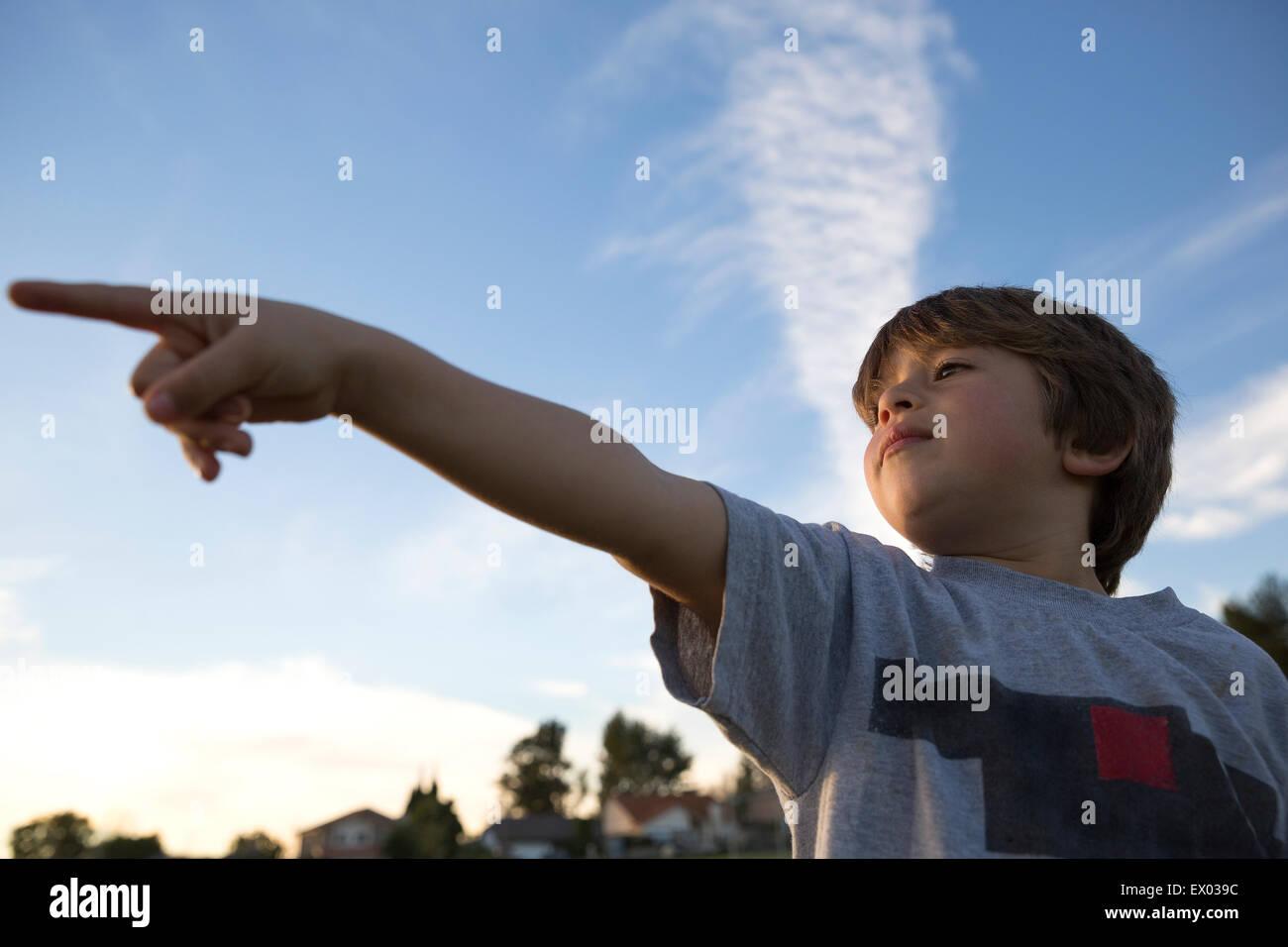 Ángulo de visión baja de boy dedo señalador en estacionamiento Imagen De Stock