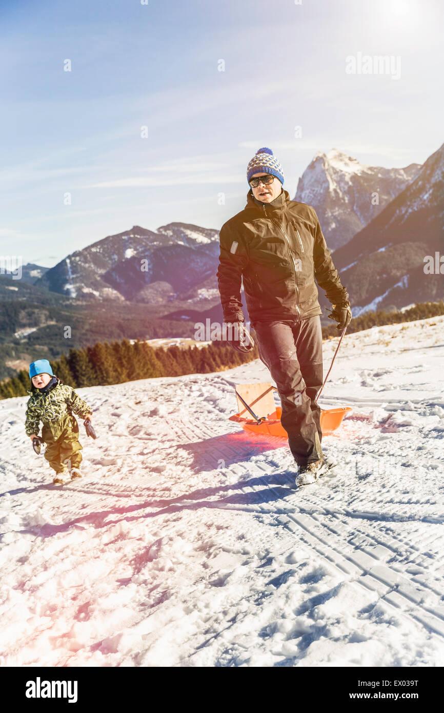 El hombre tirando del trineo sobre la nieve, Achenkirch, Tirol, Austria Imagen De Stock