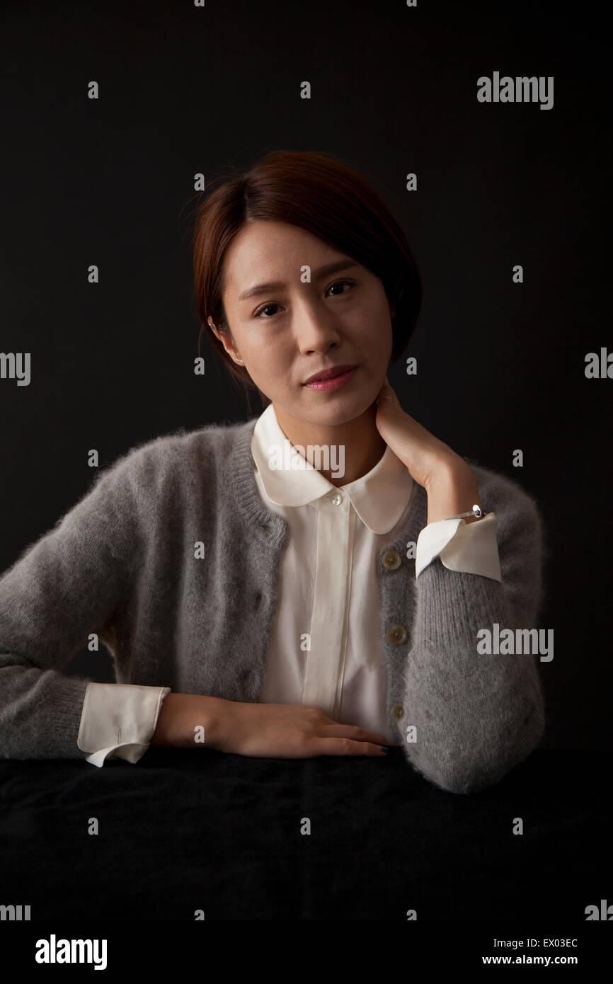 Retrato de mujer sentada en la mesa Foto de stock