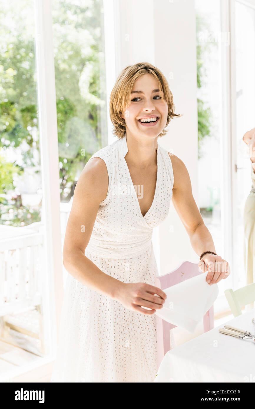 Mujer servilletas plegables en mesa de comedor para la fiesta Foto de stock