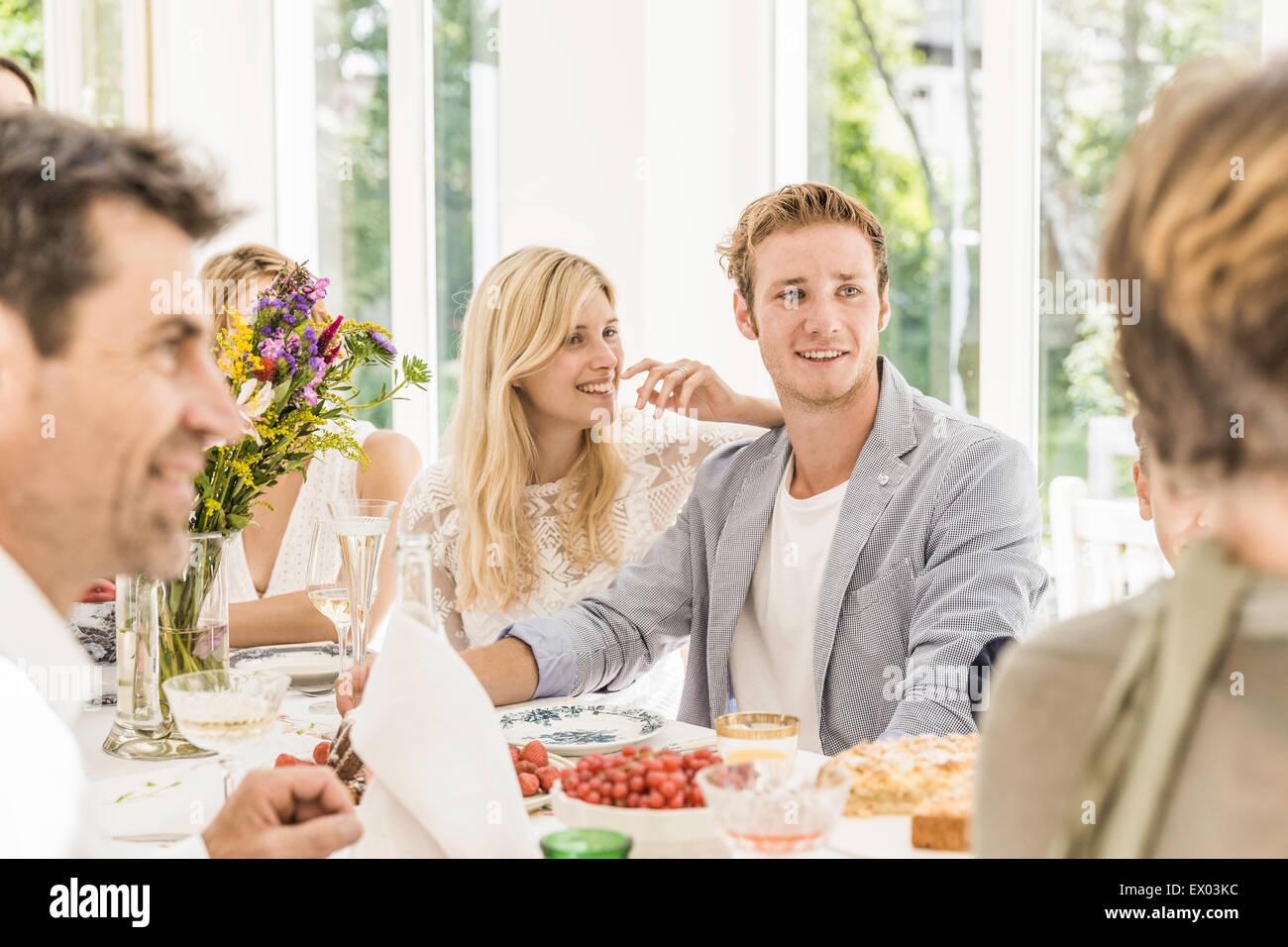 Los adultos de la familia conversando en la mesa de fiesta de cumpleaños Imagen De Stock