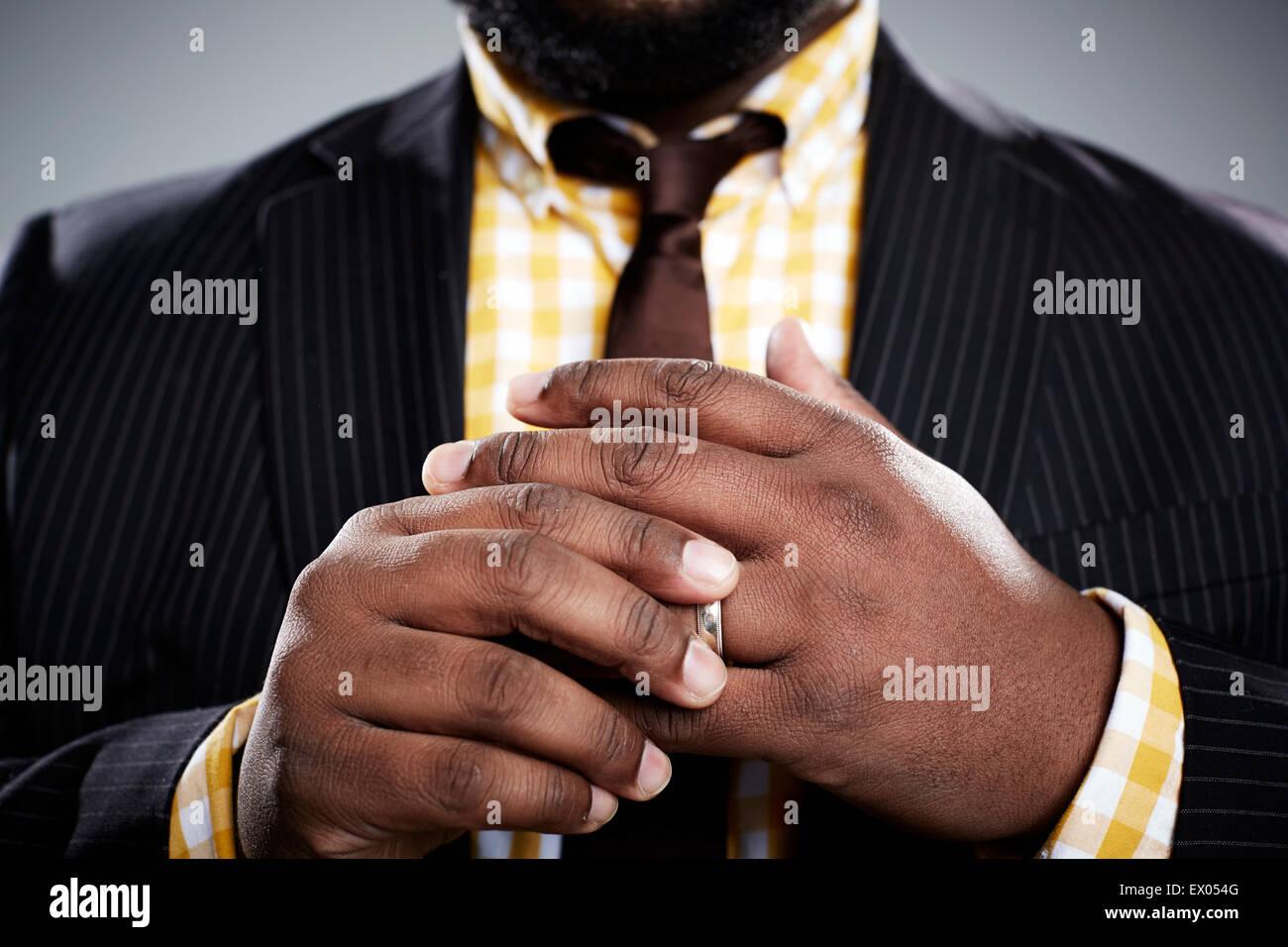 Close Up retrato de estudio de mediados de adulto empresario tocando su anillo de bodas Imagen De Stock