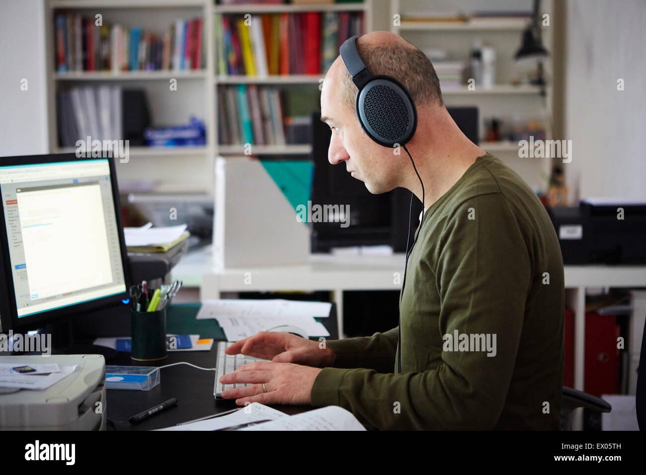 Hombre maduro trabajan en creative studio usando audífonos Imagen De Stock