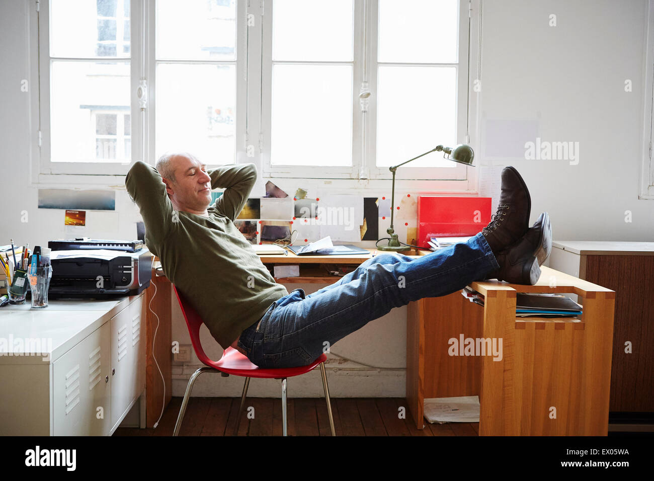Hombre maduro, sentado con los pies para arriba en la recepción Imagen De Stock