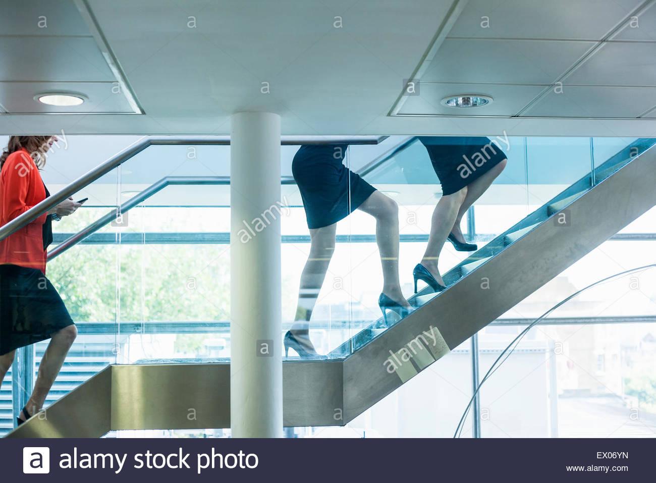 Las piernas de mujeres empresarias subiendo escaleras de oficina Imagen De Stock