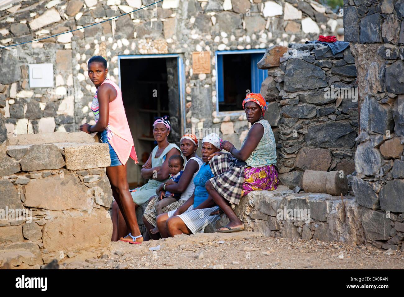 Las mujeres y las niñas criollas sentado en frente de su casa de piedra en la aldea Rebelados en la isla de Imagen De Stock