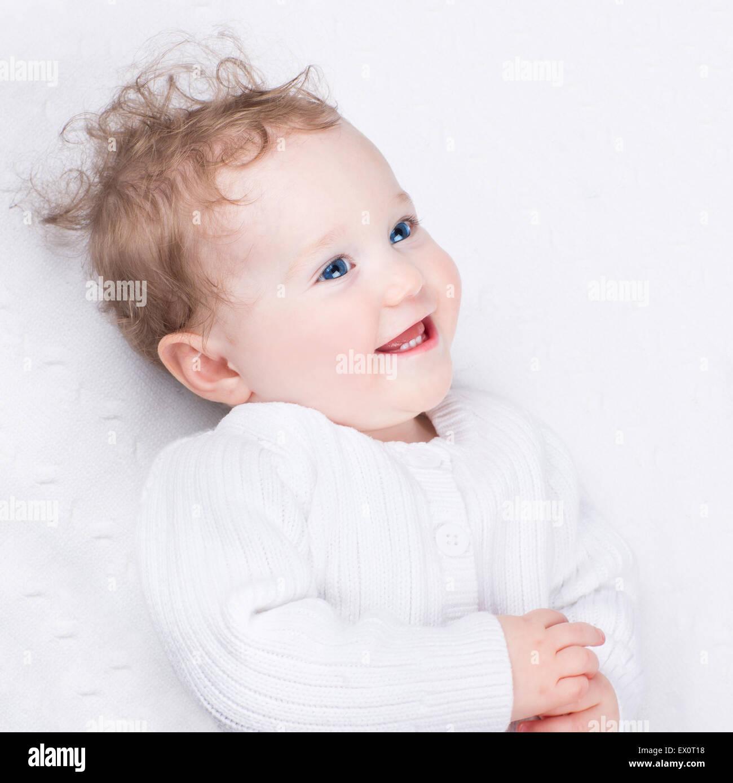 Risa adorable pequeño bebé vistiendo una cálida chaqueta tejida en una sábana blanca Imagen De Stock