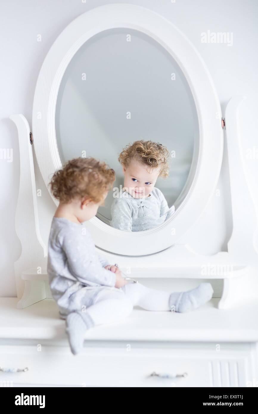 Funny lindo bebé niña viendo su reflejo en un dormitorio blanco con un bonito espejo redondo Imagen De Stock