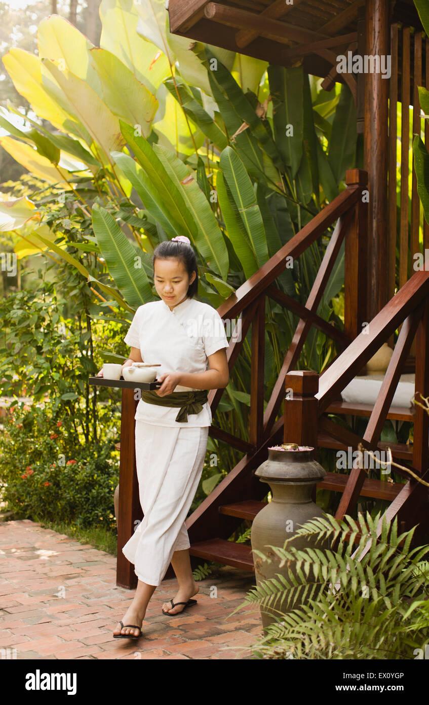 Un terapeuta lleva té abajo de los pasos de una de las cuatro salas de tratamientos en La Residence Phou Vao. Imagen De Stock