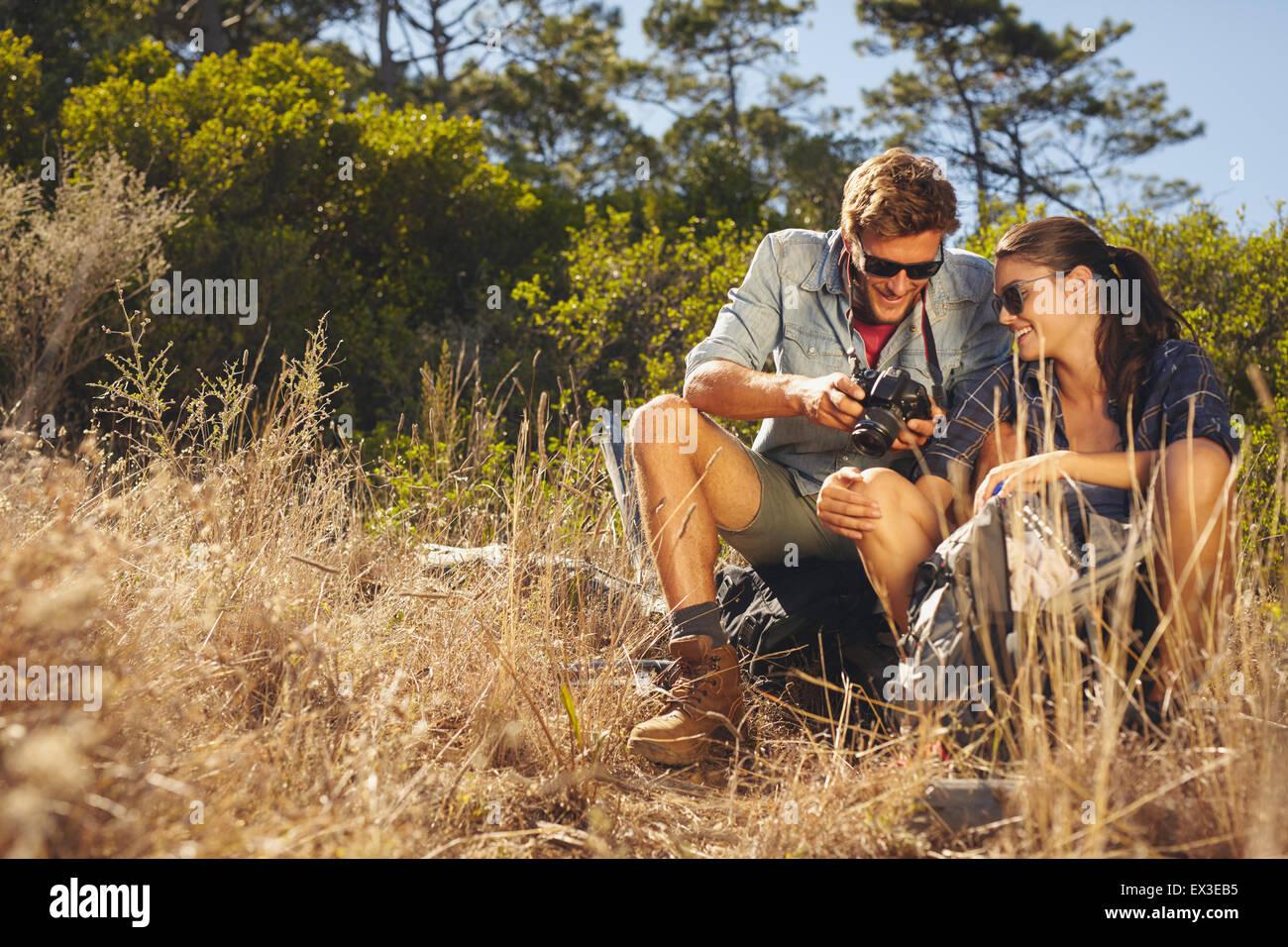 Pareja joven afuera mirando fotos en la cámara. Un hombre y una mujer caucásica de excursión tomando Imagen De Stock