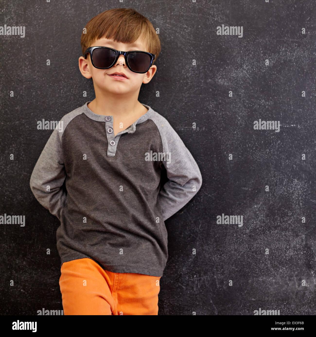Retrato de niño inteligente smirking con gafas de sol. Cool kid en tonos recostada sobre una pizarra, mirando a Foto de stock