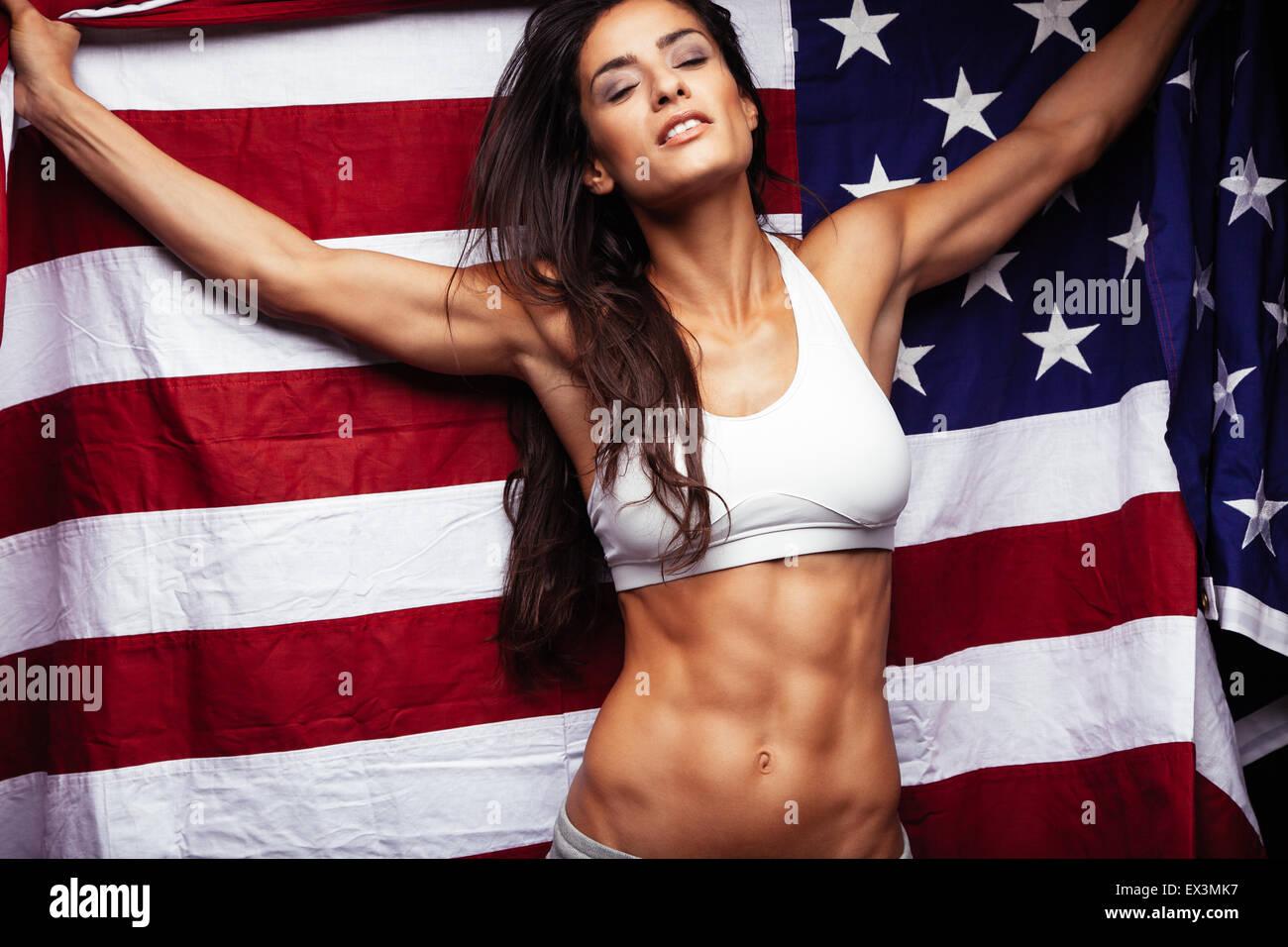 Deportivo joven sosteniendo la bandera americana. Fitness femenino perfecto con abs. Imagen De Stock