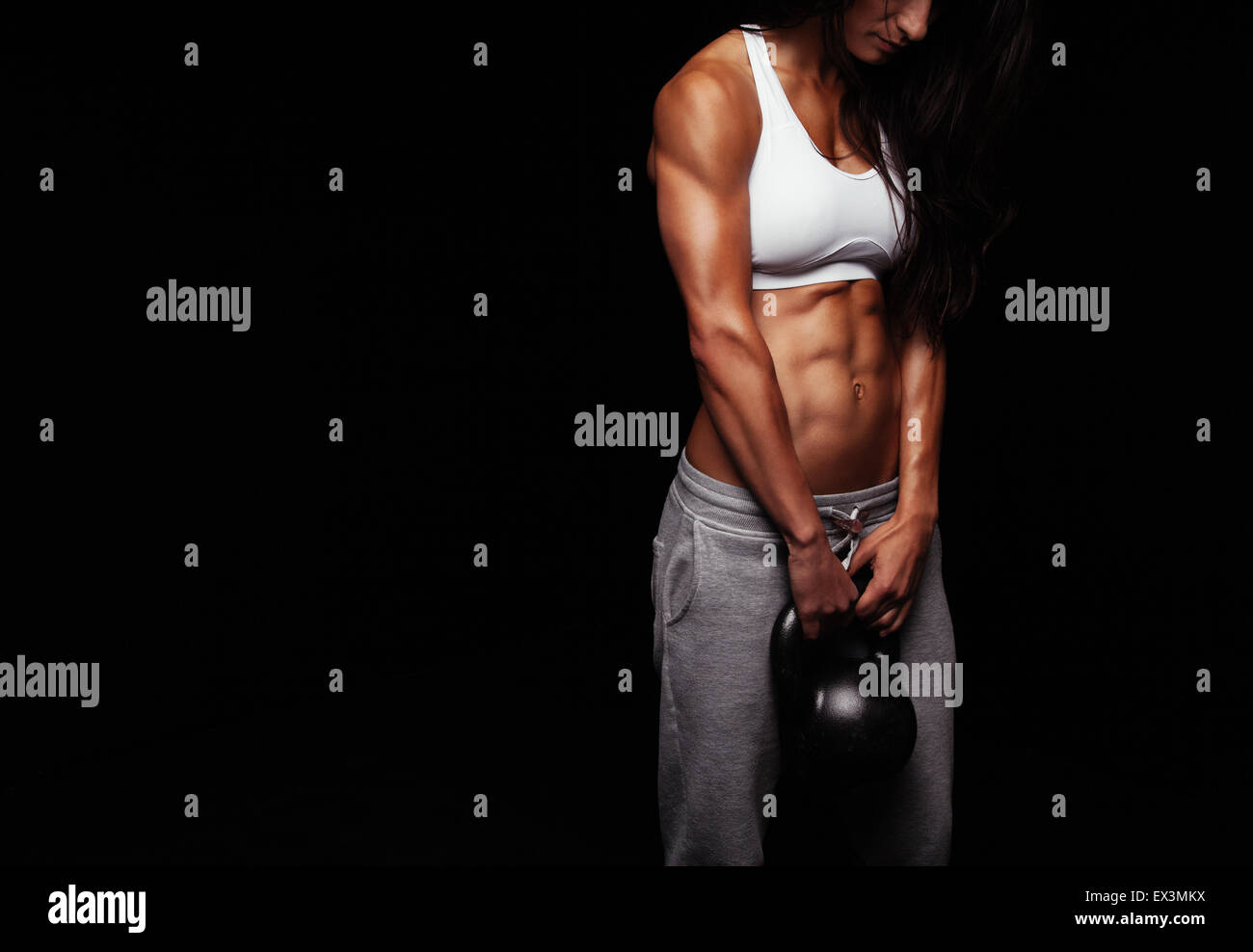 Captura recortada de la atleta femenina haciendo ejercicio body building con hervidor bell sobre fondo negro. Imagen De Stock