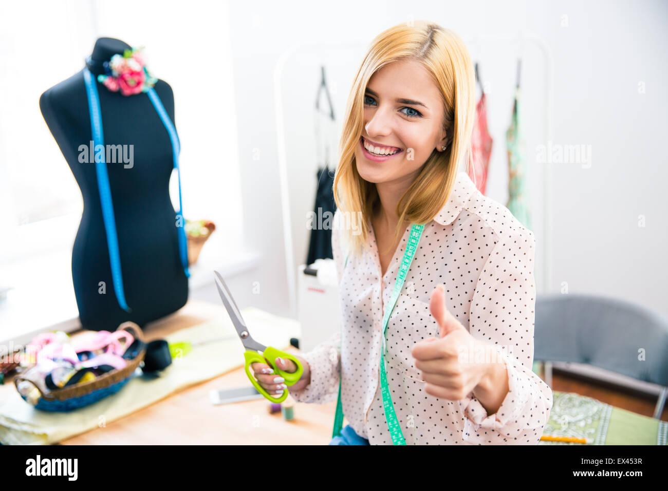 Mujer sonriente sastre de pie en taller y mostrando el pulgar hacia arriba Imagen De Stock